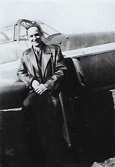 Black and white photo of a man in a long coat, leaning against a plane