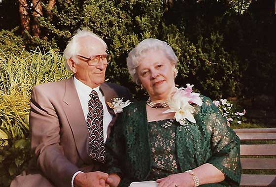 An elderly couple seated on a park bench outdoors, holding hands, each wears a boutonniere
