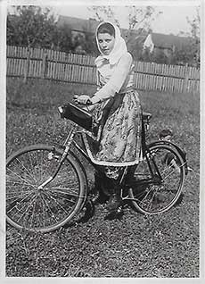 A black and white photo of a woman in a flowered skirt and head scarf, standing with a bicycle
