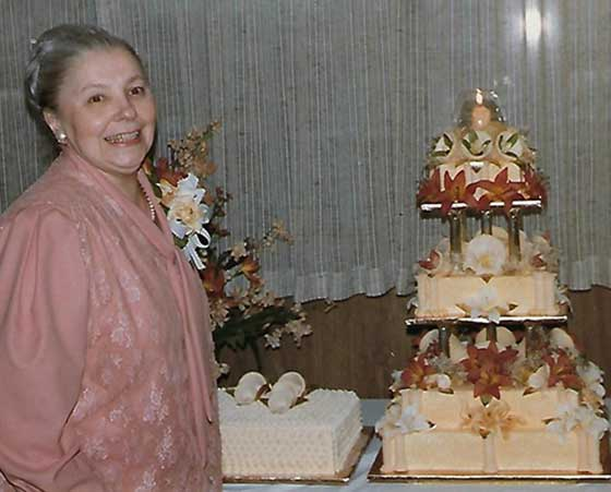A woman in a pink dress stands smiling next to a three-tiered wedding cake, elaborately decorated
