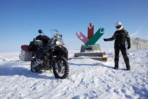 A motorcyle and a man wearing a motorcycle suit and helmet against a frozen terrain.