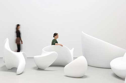 Flowing white sculptures rest across the floor, and woman is sitting on one of them.