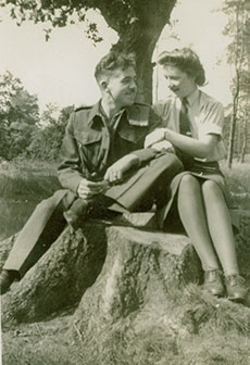 A man and woman in military uniform sit arm in arm on a tree stump.
