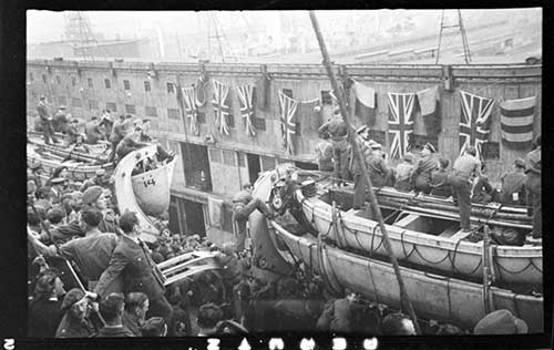 A ship filled with men in uniform docking next to a building strung with Union Jack flags.