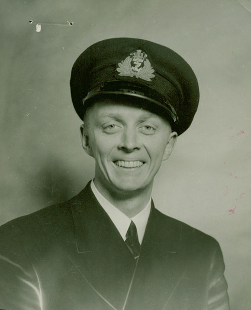A man smiling in a navy uniform.