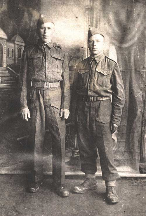 Two men wearing military uniforms stand together.