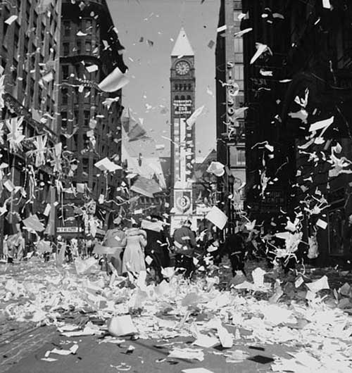 A city street is showered with paper and confetti and a clock tower in the background.