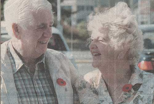 Scan of a newspaper photograph of an older man and older woman smiling at each other, both with poppies pinned to their lapels.