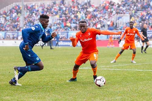 Two soccer players, one in a blue uniform and one in an orange uniform face off for the soccer ball.
