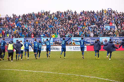 A large crowd of cheering fans fill bleachers, on the field below a line of soccer players in blue uniforms raise their hands to the crowd.