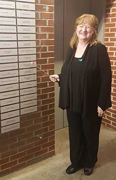A woman stands next to a brick wall that is lined with sliver plaques engraved with names.