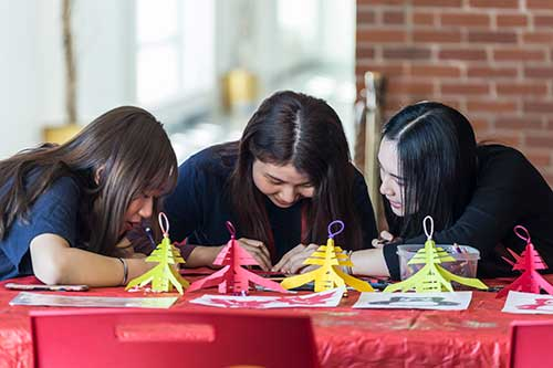 Three young ladies are at a table, doing crafts.