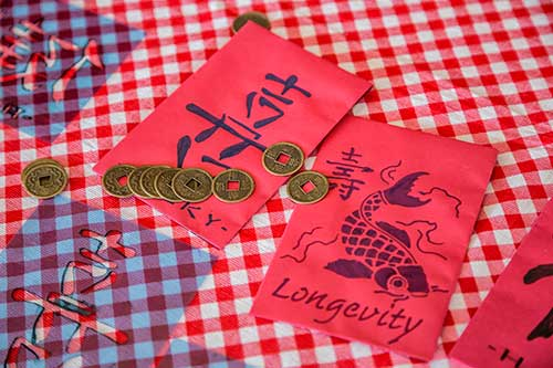 Two decorated red envelopes with coins nearby.