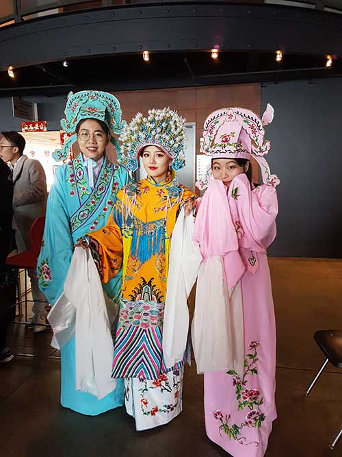 Three young girls dressed in traditional costumes celebrate Lunar New Year.