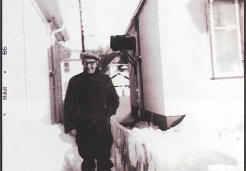 A very old photograph of a man standing between two banks of snow.