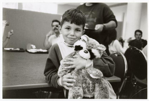 A smiling boy holds a stuffed raccoon toy.