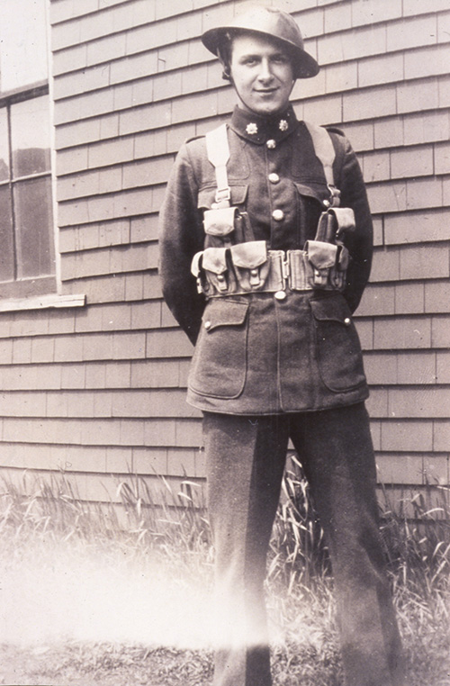 A man in a WWII Canadian army uniform including helmet stands proudly with his arms behind his back, the backdrop is the clapboard wall of a house