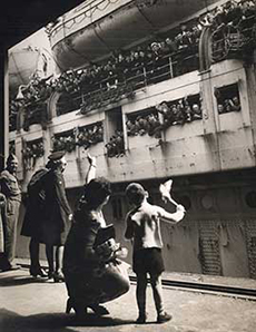 Old black and white war-time photo, showing a troop ship docking with hundreds of waving soldiers and a little boy and his mother waving back at them from the platform, while a serviceman looks on.