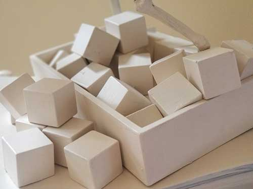 A close up view of a box filled with cubes, all the same shade of beige.