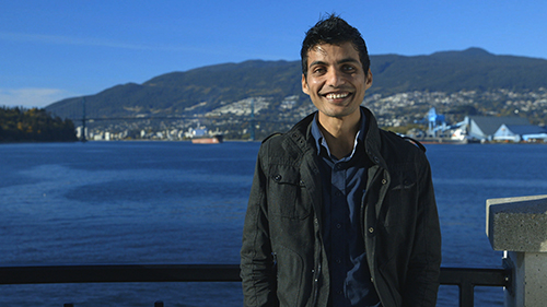 A smiling man standing against a railing, behind him there is water, city scape and a mountain.