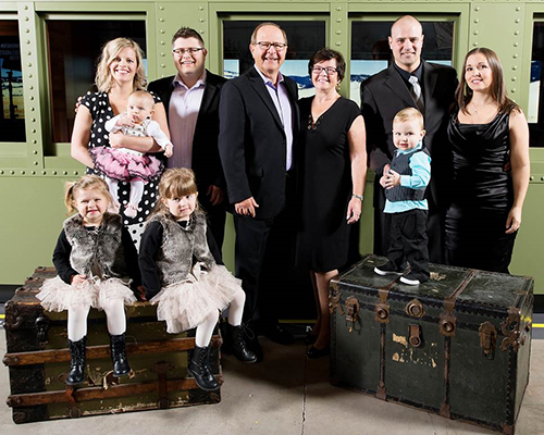 A man and woman stand in between their adult children and grandchildren.