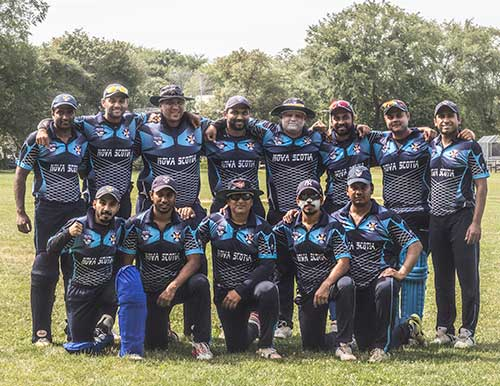 A team photo of two rows of Cricket players wearing blue jerseys that say Nova Scotia on the front.