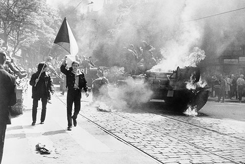 Black and white photo of people marching down a street, one person waves a flag, a tank in the background appears to be on fire