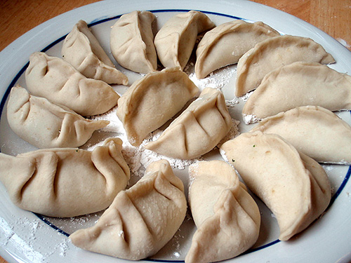 A plate full of Chinese dumplings sprinkled with flour