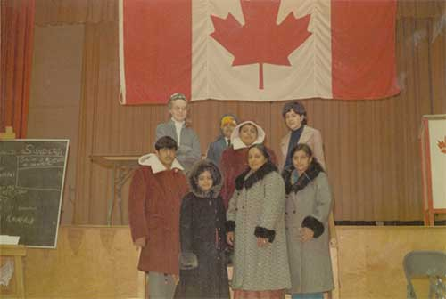 A group of people, many of them wearing fur lined winter coats, stand indoors in front of a large Canadian flag.