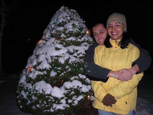 A woman in a yellow coat is embraced from behind by a man, they are smiling standing next to a snow covered hedge.