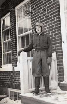 A young person with trousers tucked into winter boats, wearing gloves and a hat stands on the snow covered front steps of a house.