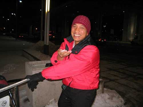A smiling man in a red coat holds snow in his bare hand.