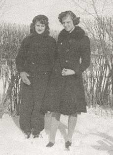 A black and white photograph of two young women wearing winter coats standing in ankle-deep snow with trees and bushes in the background.
