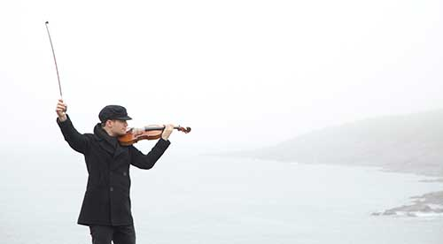 A man wearing a dark jacket and cap is holding a violin and bow, in the background we see an ocean shoreline.