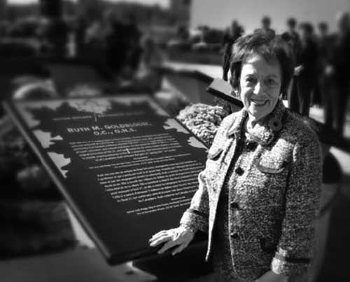Black and white photo of a senior woman wearing a tweed jacket next to a metal plaque.