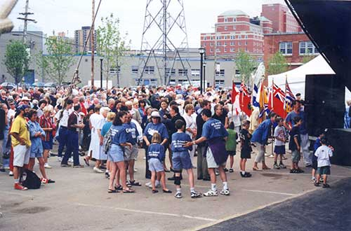 A large crowd of people gathered in a parking lot, nearby a line of flags, speakers and an event tent.
