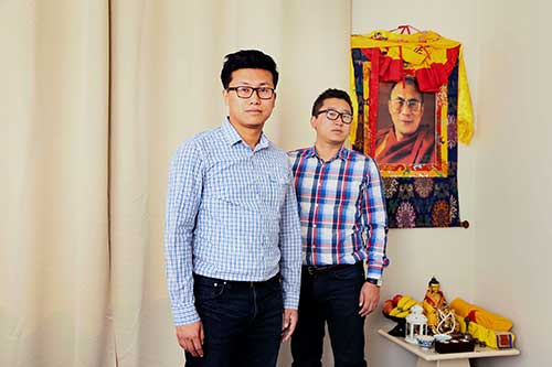 Two men looking seriously at the camera, a framed portrait of the Dalai Lama hangs in the background