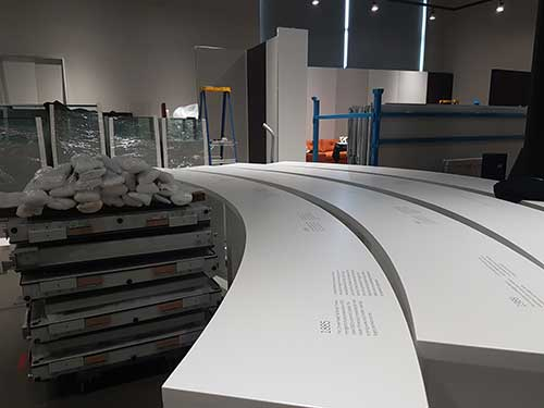 Curving exhibition panels are lined up next to stacks of pallets and glass display cases.