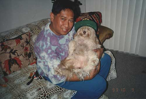 A dark haired man in a tie-dye shirt cradles a long-haired dog. The dog is wearing a baseball cap.