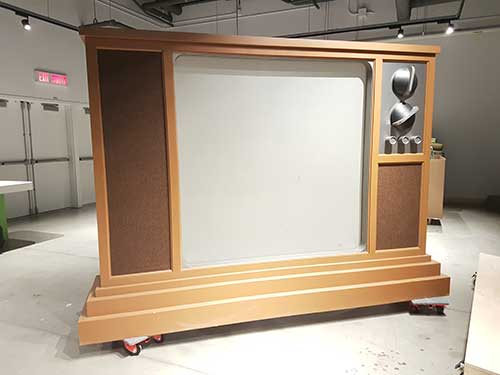 An oversized replica of a vintage wooden TV sits in an exhibition foyer.