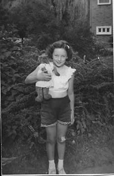 A young girl in a white blouse and shorts stands in a garden holding a teddy bear who is also wearing a white dress.