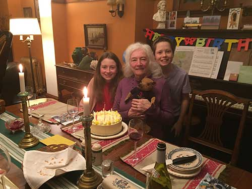 An older woman seated holding a teddy bear, a young girl and young boy are next to her and in front of her is a yellow birthday cake.