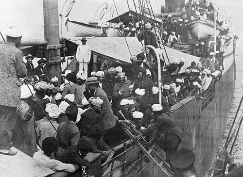 black and white image of a ship filled with passengers, many wearing turbans