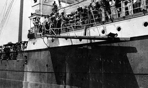 black and white photo of a ship, with passengers lined along the railing