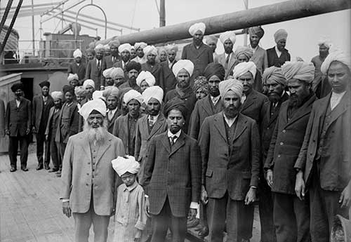black and white photo of a large group of men, and one young boy in the front, staring solemnly at the camera. Many wearing suits and turbans.