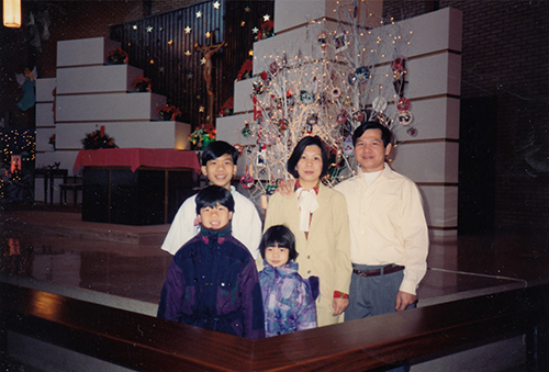A man, woman, two boys and a girl stand together in front of an altar decorated with holiday ornaments.