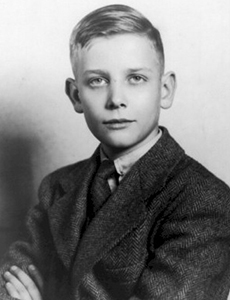 Portrait of a young blond boy wearing a suit.