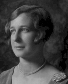 Old portrait of a young woman wearing pearls and looking off to her side.