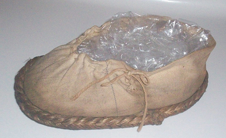 Close up of a moccasin-like shoe with stitching on the side.