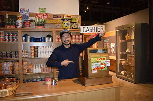 A young man sits at an exhibit and points rto a sign that says Cashier.